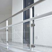 Geländer aus weiß lackiertem Stahl mit Glasscheiben in einem Treppenhaus
